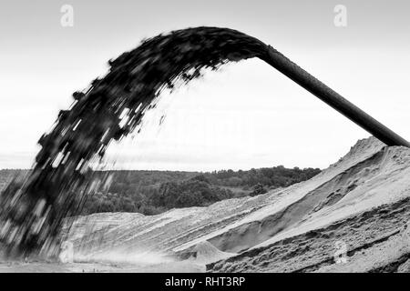 Industrial extraction of sand for construction. From the pipe wabrasives sand with water under strong pressure - Stock Photo