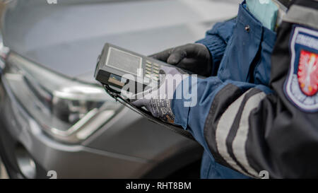 A male German policeman from Frankfurt in uniform writes a fine on the road. - Stock Photo