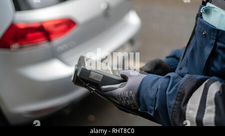 Male German policeman in uniform writes a fine on the road - Stock Photo