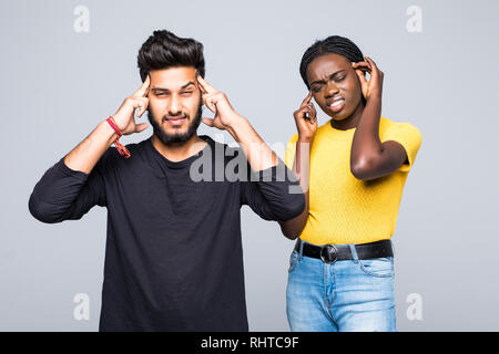 Portrait of mixed race couple sort out relationships, look in displeasure at each other, have quarrel stand against white background. Interracial fami - Stock Photo