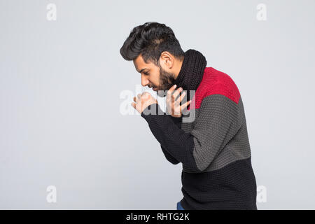 Young indian man in gray sweater, scarf sneezing or coughing covering mouth with hands isolated on grey wall background. - Stock Photo