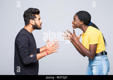 Excited surprised young interracial couple dressed in identical clothes and eyeglasses keeping clenched fists at their faces, screaming, opening mouth