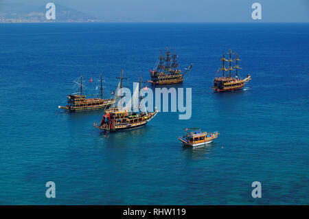 Tourist sail boats in turquoise waters of the Mediterranean sea beside the Turkish ancient fortress Alanya. Antalya, Turkey - Stock Photo