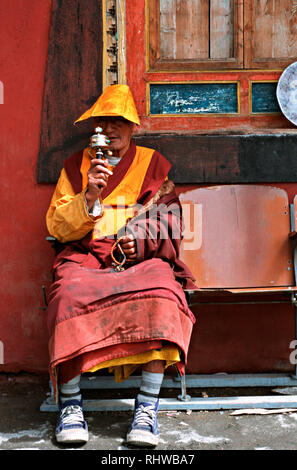 A Tibetan monk taking a rest and spinning his prayer wheel on his daily circling of the Lagong monastery in Sichuan. Circling places with auspicious p - Stock Photo