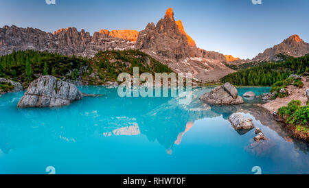 stitched wideangle panorama of a stunning sunset at Lago di Sorapis in the Italian Dolomites - Stock Photo
