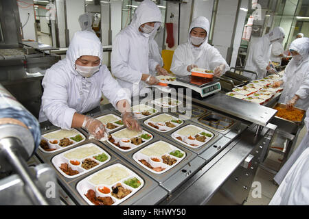 (190204) -- QINGDAO, Feb. 4, 2019 (Xinhua) -- Staff members prepare food in a catering management company for high speed trains in Qingdao, east China's Shandong Province, Feb. 3, 2019. Packed meals on high speed trains are prepared by specialist catering service companies. Each meal is checked by taste, nutrition and price before it is served to passengers. (Xinhua/Li Ziheng) - Stock Photo