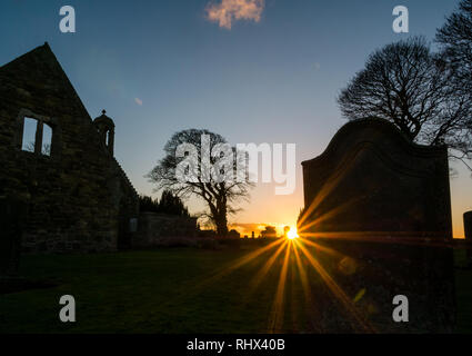East Lothian, Scotland, United Kingdom, 4th February 2019. UK Weather: The sun bursts through silhouettes of the ruined walls of Gladsmuir old parish church and churchyard with old gravestones at sunset in Winter - Stock Photo