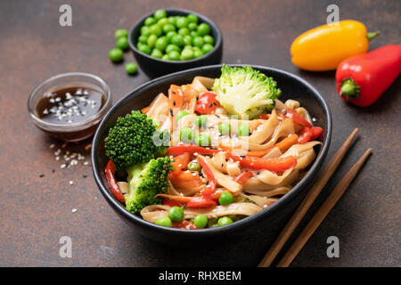 Asian udon noodle stir fry with broccoli, green pea, carrot and pepper in bowl. Tasty oriental asian food - Stock Photo