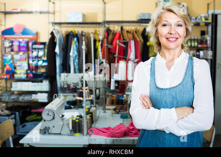 friendly smiling mature blonde woman tailor standing in sewing studio - Stock Photo