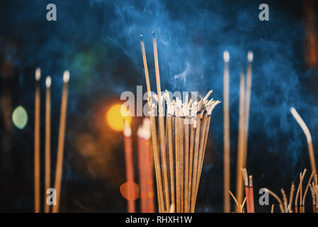 Incense sticks burning with smoke close-up view - Stock Photo