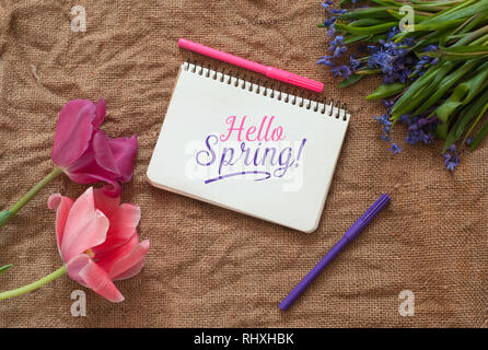 Two tulips with Scilla bifolia and blank notepad with colored pens on a sackcloth texture. Hello Spring Text Template - Stock Photo