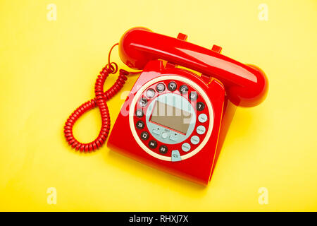 A red retro telephone from above against a yellow background. - Stock Photo