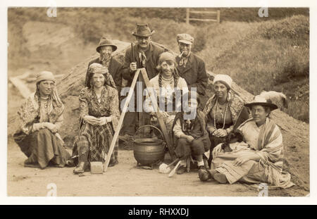 Early 1900's postcard of family dressed as gypsies in traditional dress, blackened faces, stitting next to cooking pot, posing for a group photograph,  U.K. circa 1920's - Stock Photo