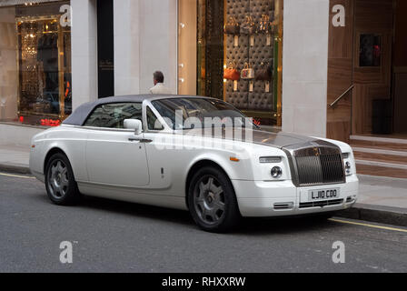 London, United Kingdom - February 25, 2010: car parked at shop window. Luxury automobile on city street. Motor transport and transportation. Travelling or trip and wanderlust. - Stock Photo