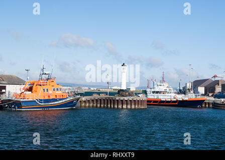 Kirkwal, United Kingdom - February 19, 2010: sea harbor with ships and lighthouse on blue sky. Water transport and transportation. Travelling by sea. Summer vacation on island. Wanderlust and journey. - Stock Photo