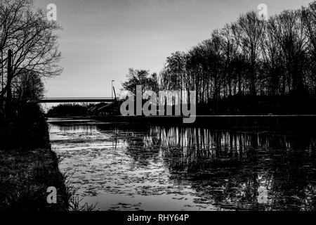 Dramatic and monochrome sunrise over a Beautiful early winter landscape with a frozen river or canal, treelined riverside and grass at sunrise creatin - Stock Photo