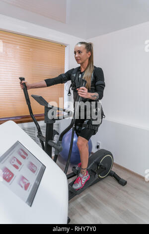 Athletic slim girl does exercises on a simulator with an electro-muscular stimulator, EMS - Stock Photo