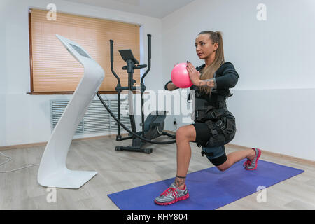 Young girl in an electric muscular simulation suit doing a squat in the gym - Stock Photo