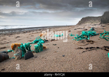 Discarded fishing nets embedded in sand on UK beach a major form of plastic pollution. - Stock Photo