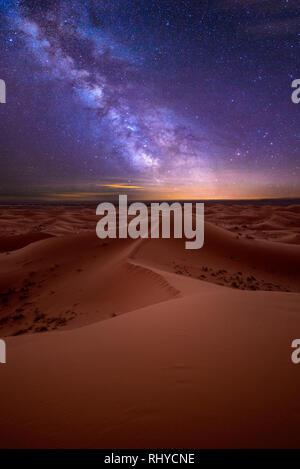 Amazing milky way over the dunes Erg Chebbi in the Sahara desert near Merzouga, Morocco. Beautiful sand landscape with stunning sky stars night - Stock Photo