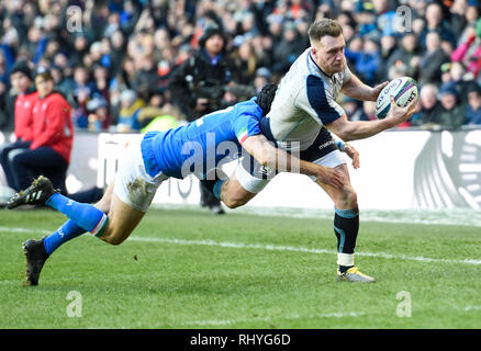 Scotland's Stuart Hogg gets past Italy's Ian McKinley to touch down but the try was disallowed by referee Luke Pearce during the Guinness Six Nations match at BT Murrayfield Stadium, Edinburgh. - Stock Photo