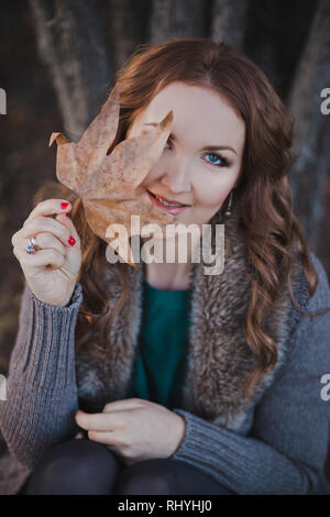 Absolutely beautiful lady woman with brunette hair deep blue eyes pink cheeks and rose pout lips sitting in autumn forest on foliage ground posing for - Stock Photo