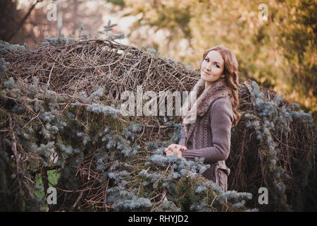 Beautiful genuine lady mystic with curly brunette hairs and adorable eyes dressed in fancy stylish warm clothes with fur on neck lonely posing sit for - Stock Photo