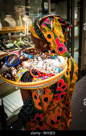 Black woman street seller in traditional dress with basket of trinkets on her shoulder Valencia Spain - Stock Photo