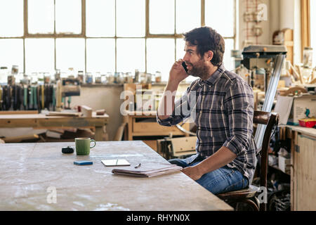 Woodworker sitting at a workbench talking on his cellphone - Stock Photo