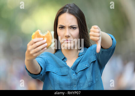 Front view of annoyed woman holding a burger with thumb down in the street - Stock Photo