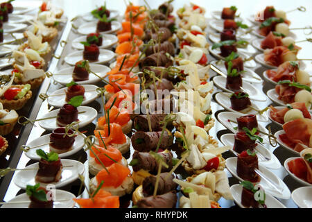 Appetizers setting on the white plates served for food reception - Stock Photo