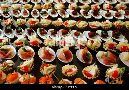Starters and snacks setting on the white plates served for buffet reception - Stock Photo