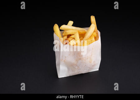 French fries in a white paper box on black background. - Stock Photo
