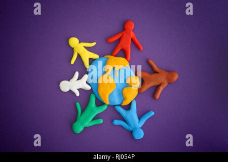 Group of people around the world. Concept image. People and Earth are made out of play clay (plasticine). Close up. - Stock Photo