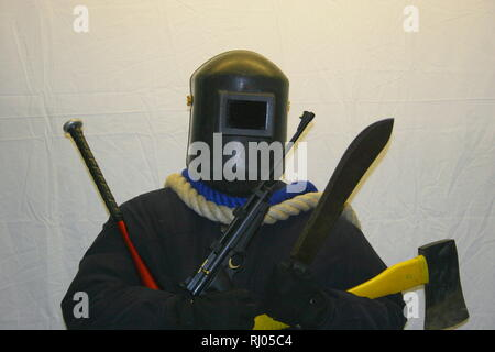 Weapons. Knife crime. Knives. Guns. Rifle. Air weapons. Blunt instrument. Baseball bat. Axe. Machete. Rope. Heavily armed man. Face covering. Anonymity. Violent society. Sick society. Concepts. Conceptual. Education. Mask. Welders mask. Going equipped. Tooled up. Offensive weapons Gangs. Armed gangs. Book cover. - Stock Photo