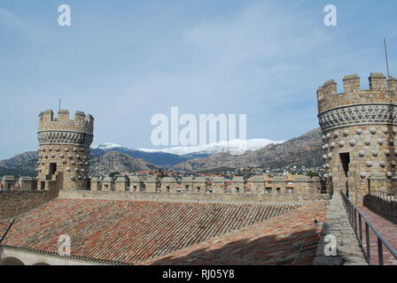 A view of mountains and turrets on the rooftop terrace of the castle of Manzanares el Real in central Spain - Stock Photo
