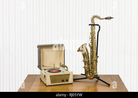 Old record player and saxophone on wood table. - Stock Photo