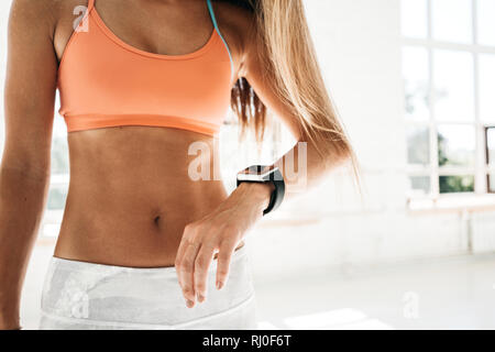 Photo fit woman after workout session checks results on smartwatch in fitness app. Sporty girl wearing sport tracker wristband arm - Stock Photo