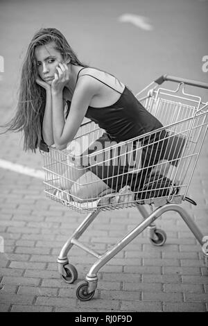 Sad girl in empty shopping trolley at market parking - Stock Photo