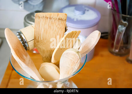 Wooden kitchen utensils in a glass container. Kitchen interior shot. Home decor and cooking concept - Stock Photo