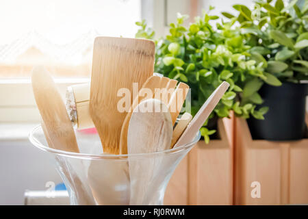 Wooden kitchen utensils in a glass container with a grass in the background. Kitchen interior shot. Home decor and cooking concept - Stock Photo