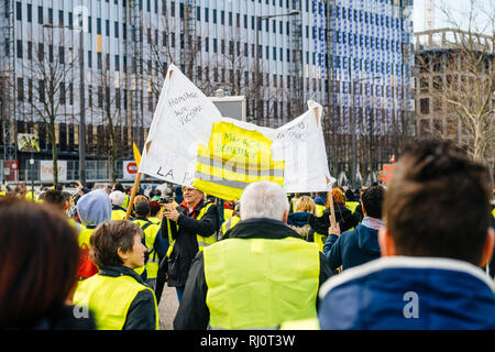 STRASBOURG, FRANCE - FEB 02, 2018: People demonstrating marching with placards during protest of Gilets Jaunes Yellow Vest placard with inscription Macron resignation  Stock Photo