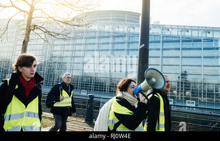 STRASBOURG, FRANCE - FEB 02, 2018: Woman yelling on megaphone loudspeaker demonstrating marching with placards during protest of Gilets Jaunes Yellow Vest manifestation European Parliament Stock Photo