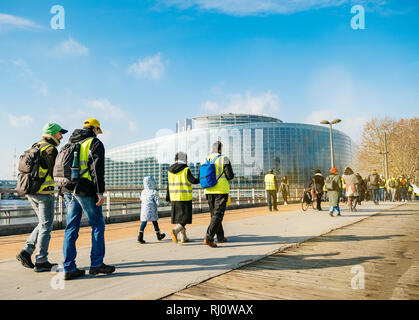 STRASBOURG, FRANCE - FEB 02, 2018: People demonstrating walking toward European Parliament during protest of Gilets Jaunes Yellow Vest manifestation anti-government demonstrations Stock Photo