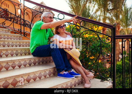 Senior couple sitting on stairs on hotel territory and pointing at view. People enjoying vacation. Traveling concept - Stock Photo