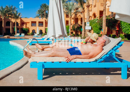 Senior couple relaxing by swimming pool. People enjoying vacation in Egypt. All inclusive - Stock Photo