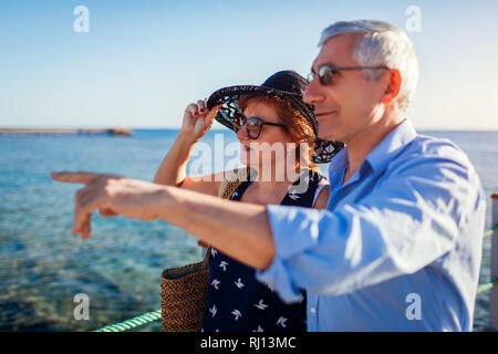 Senior couple walking on pier by Red sea. People enjoying vacation. Valentine's day - Stock Photo