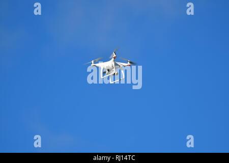A Drone against a plain blue sky - Stock Photo