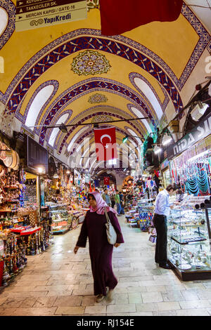 Istanbul, Turkey : A Turkish woman walks past shops inside the Grand Bazaar (Kapalıçarşı) one of the largest and oldest covered markets in the world w - Stock Photo