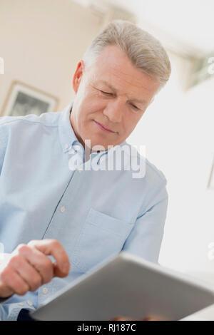 Mature man using digital tablet at home - Stock Photo